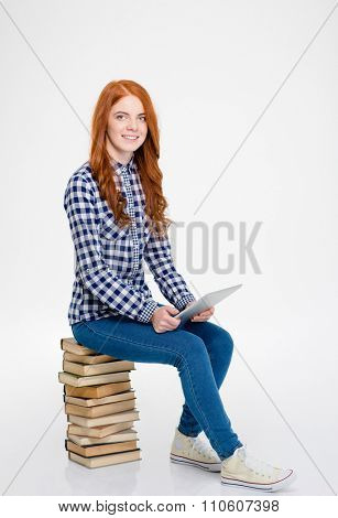Cheerful positive curly readhead lady in plaid shirt and jeans sitting on stack of books and using tablet over white background