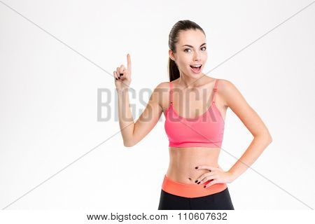 Beautiful happy young sportswoman in tracksuit pointing up and having an idea over white background