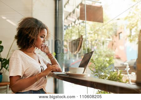 Young Black Woman At Cafe Using Laptop