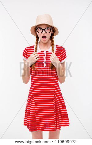 Funny surprised redhead girl with two braids in boonie hat and round glasses standing over white background