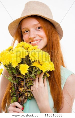 Portrait of happy cheerful pretty natural girl with long red hair in boonie hat holding flowers