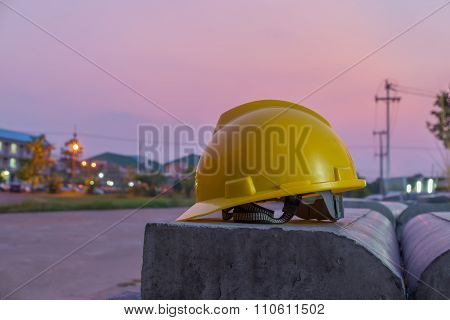 Yellow safety helmet on city sunset background.