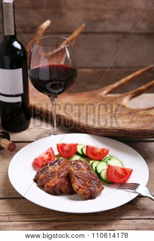 Roasted venison fillet and fresh vegetables on plate, on wooden background