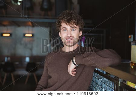 Charming joyful content handsome positive charismatic young man in brown sweetshirt posing in cafe