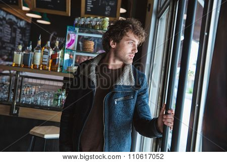 Handsome pensive young curly man in black jacket looking through glass door in cafe