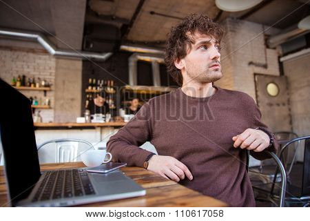 Attractive curly thoughtful concentrated handsome young male in brown sweetshirt sitting and looking away from laptop