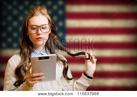 Beautiful young woman with ebook on USA flag blurred background