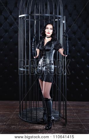 Mistress Girl In Leather Clothing Is Standing Near The Cage.