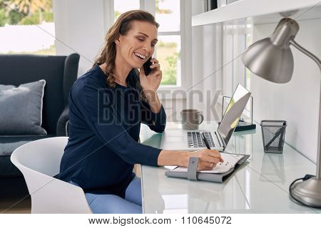 Casual businesswoman working remotely from home office writing on notepad and talking on mobile phone.