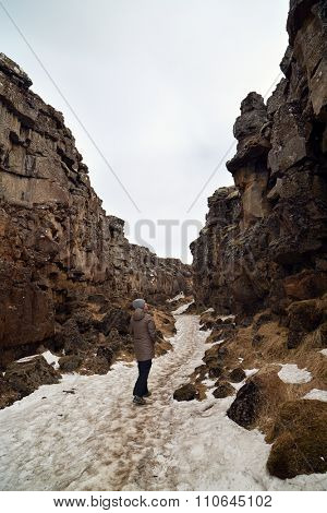 Independent Tourist walking through the crack between tectonic plates in Thingvellir national park, Iceland