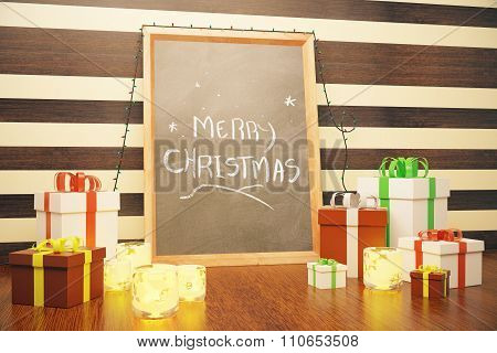 Merry Christmas Inscription On Picture Frame With Gift Boxes And Candlesticks On Wooden Floor
