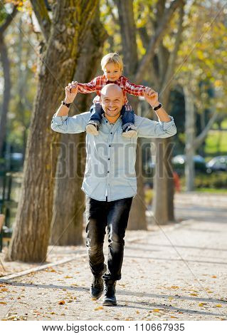 Young Happy Father Carrying  Little Son On Shoulders Having Fun
