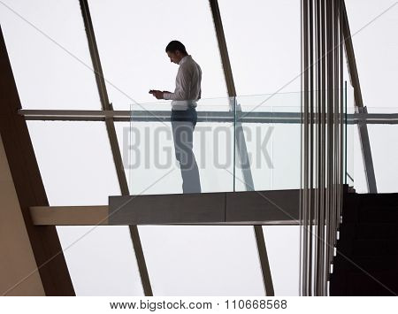 young successful business man in penthouse working on tbalet,  modern bright duplex office apartment interior  with staircase and big windows poster