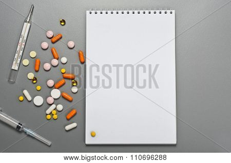 Open Notebook With Tablets, Capsules, Thermometer And Syringe