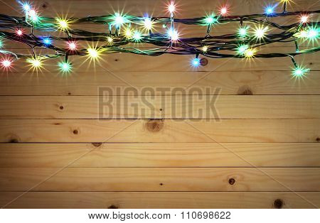 Christmas light boarder on wooden background.