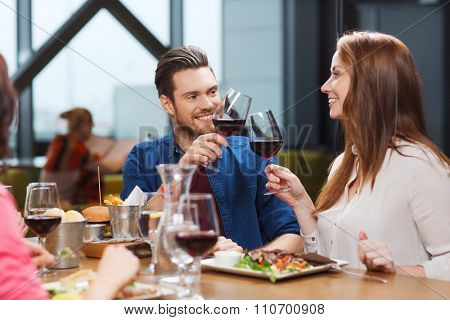 leisure, eating, food and drinks, people and holidays concept - smiling couple having dinner and drinking red wine at restaurant