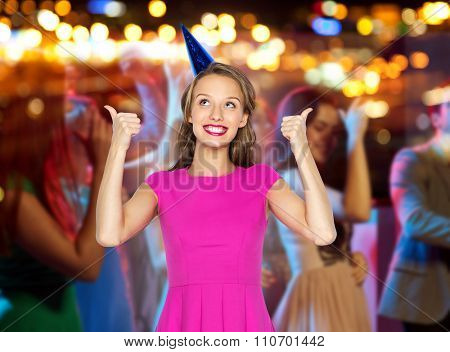 people, holidays and celebration concept - happy young woman or teen girl in pink dress and party hat showing thumbs up at night club party over crowd and lights background