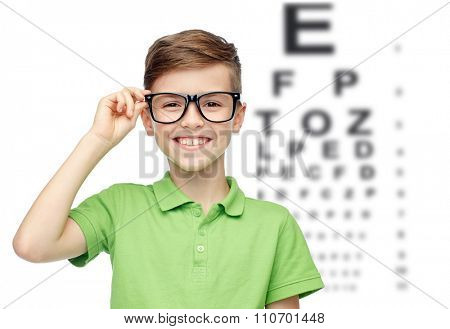 childhood, vision, eyesight and people concept - happy smiling boy in green polo t-shirt in eyeglasses over eye chart background