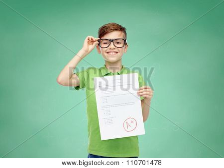 childhood, school, education and people concept - happy smiling boy in eyeglasses holding paper with test result over green school chalk board background