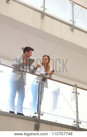 Young businesspeople talking in balcony on modern building, smiling.