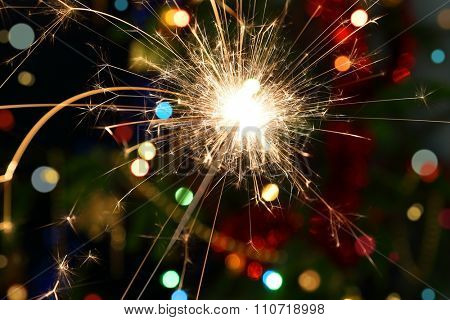 sparkler burning on background decorated Christmas tree