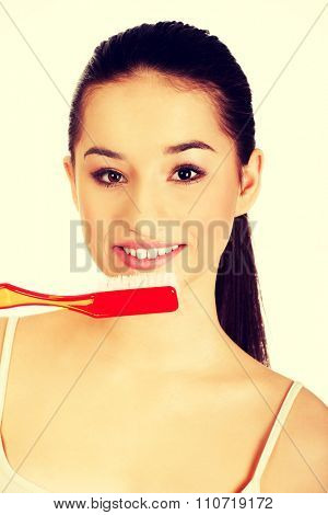 Woman brushing her teeth with enormous brush.