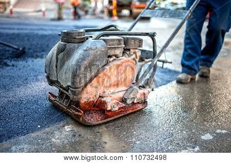 Asphalt Worker At Road Construction Site With Compactor Plate And tools