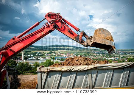 Close-up Of Industrial Excavator Loading A Dumper Truck With Soil and earth from construction site