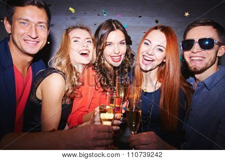 Ecstatic friends toasting with champagne at party