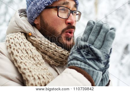 Asian guy in winterwear and gloves trying to warm his hands outside
