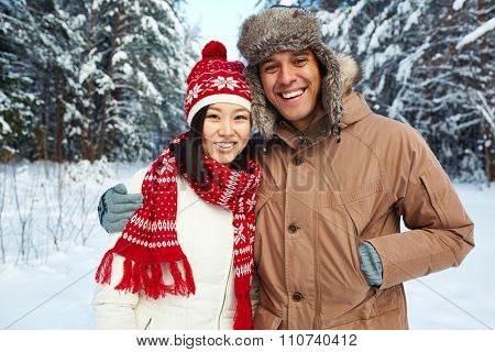 Happy young couple in winterwear looking at camera in natural environment
