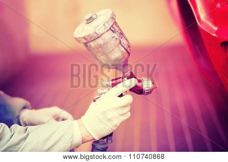 Worker Painting A Red Car In Paiting Booth Using Professional Tools