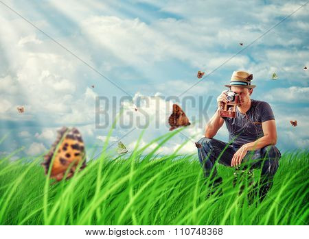 Young Man Photographing Butterflies On Camera In The Meadow