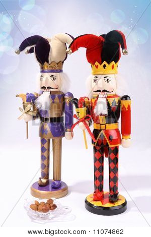 Two wooden nutcrackers with a plate of nuts