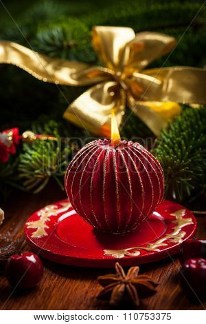 Christmas candle with balls in red tone
