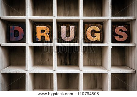 """The word """"DRUGS"""" written in vintage ink stained wooden letterpress type in a partitioned printer's drawer. poster"""