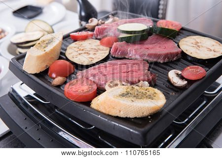 Steaks, Garlic Bread And Mushrooms On The Raclette  Cooking