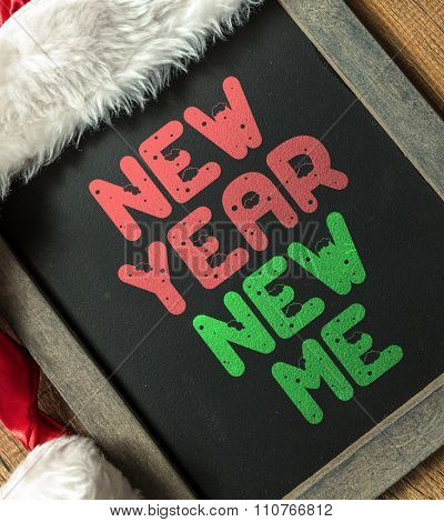 New Year New Me written on blackboard with santa hat