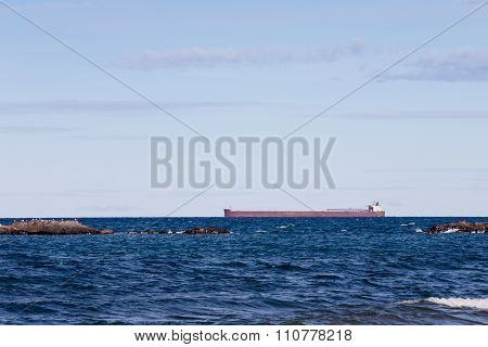 Great Lakes Ore Boat Passing Behind Rocky Outcroppings