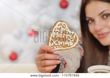 Close Up Of Christmas Heart Shape Home Cookies In Woman's Hand On Christmas Tree Background