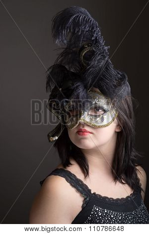 Portrait Of A Teen Girl In A Venetian Mask Embedded With Fowl Black Feathers.