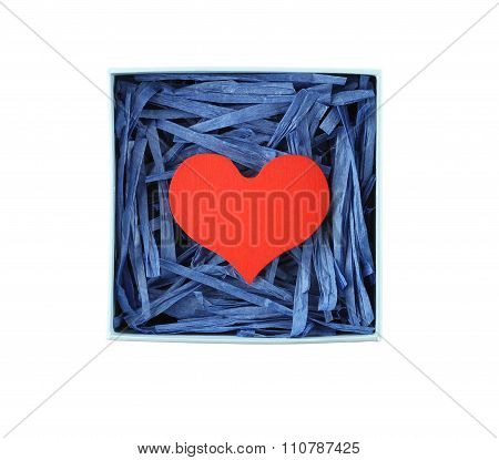 Red painted wooden heart enclosed with blue paper raffia strips in paper box