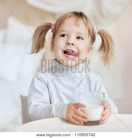 Cute little girl with milk mustache holding glass of milk