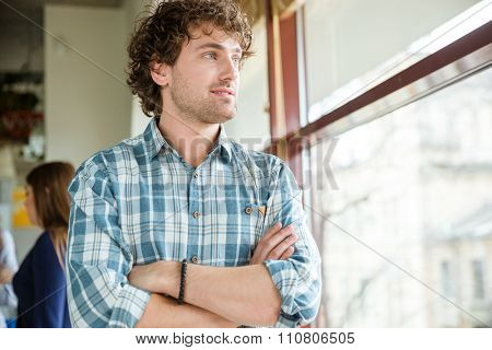 Pensive smiling young curly guy in plaid shirt standing and looking at the window with arms crossed