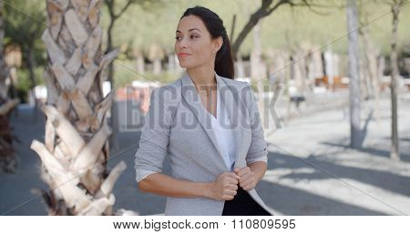 Stylish young woman in an urban park standing alongside a tropical palm tree holding the lapels of her jacket as she looks to the side