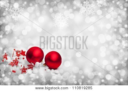 Grey christmas background with two red balls, stars and lights and falling snowflakes