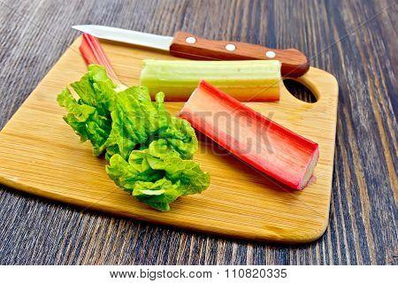 Rhubarb With Knife And Leaf On Dark Board