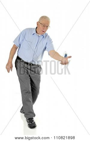 A senior man concentrating as he moves to catch his spinning yo-yo as it completes an