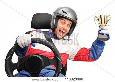 Excited car racer holding a gold trophy seated on a car seat and looking at the camera isolated on white background