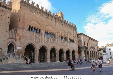 Tourists Walking Near The Ancient Buildings And Statue Of Pope Paul V On Cavour Square In Rimini, It
